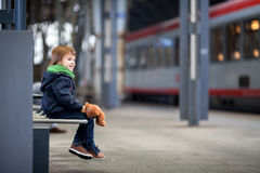 Cute boy, sitting on a bench with teddy bear, looking at a train Stock Photos