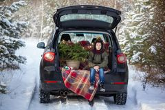 Cute boy sitting in black car at snowly winter forest. Christmas concept royalty free stock image