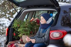Cute boy sitting in black car at snowly winter forest. Christmas concept royalty free stock photos