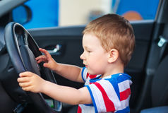 Cute boy sitting in the car and keeps the wheel Royalty Free Stock Photo