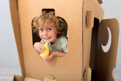 Cute boy sitting in carton rocket. Departure time. Cute adorable boy sitting in the carton rocket and looking through the window while holding ice cream of stock photos