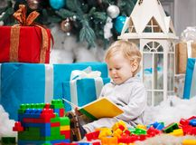Cute boy sitting at Christmas tree with a book. Cute toddler boy sitting at Christmas tree and reading book. Building blocks scattered around Royalty Free Stock Photo