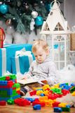 Cute boy sitting at Christmas tree with a book. Cute toddler boy sitting at Christmas tree and reading book. Building blocks scattered around Stock Photo