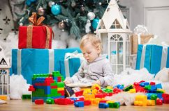 Cute boy sitting at Christmas tree with a book. Cute toddler boy sitting at Christmas tree and reading book. Building blocks scattered around Royalty Free Stock Image