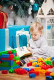 Cute boy sitting at Christmas tree with a book. Cute toddler boy sitting at Christmas tree and reading book. Building blocks scattered around Stock Photos