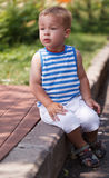 Cute boy sitting on the curb Royalty Free Stock Photography