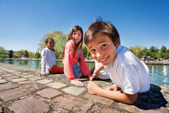 Cute boy sitting on the embankment with friends Royalty Free Stock Photography