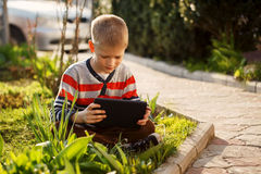 Cute boy sitting on grass in park and playing with tablet in ear Royalty Free Stock Image