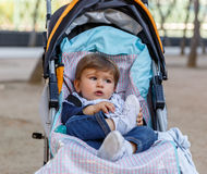 A cute boy sitting on his baby carriage, looks to the left side Royalty Free Stock Photos