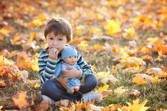 Cute boy, sitting on lawn, autumn day, eating pancakes Royalty Free Stock Photography