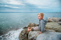Cute boy sitting near the sea. Boy sitting on a stone and looking at the sea. end of bathing season in Greece stock image
