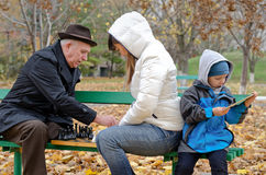 Cute boy sitting on a park bench holding a tablet computer while his mother and grandfather play chess Stock Photos