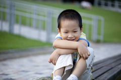 Cute boy sitting in park with smile Stock Images