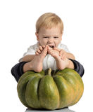 Cute boy sitting with pumpkin Stock Images
