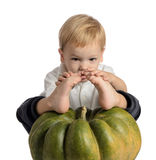 Cute boy sitting with pumpkin. On white background Stock Images