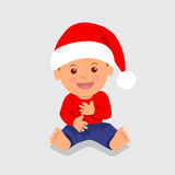 Cute boy sitting in the red Santa hat and laughs. Royalty Free Stock Images