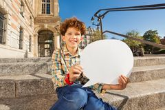 Cute boy sitting on the steps with speech bubble. Cute teenage boy sitting on the steps outdoors with blanked speech bubble Stock Photos