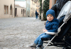Cute boy sitting in stroller Stock Images