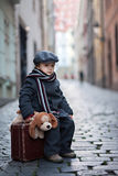 Cute boy, sitting on a suitcase, holding a teddy bear Royalty Free Stock Images