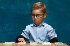 Cute boy sitting at the table and counting money. Cute fashionable boy sitting at the table and counting money. Little caucasin boy posing with cash imitating Royalty Free Stock Image
