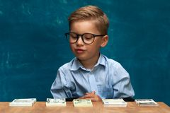 Cute boy sitting at the table and counting money. Cute fashionable child wearing eyeglasses sitting at the table and counting money. Little caucasin boy posing Royalty Free Stock Photos