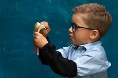Cute boy sitting at the table and counting money. Cute fashionable child wearing eyeglasses sitting at the table and counting money. Little caucasin boy posing Royalty Free Stock Photo