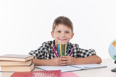 Cute boy sitting at table and holding colorful pencils. Stock Image