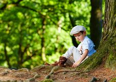Cute boy sitting under an old tree, in the forest Stock Photo