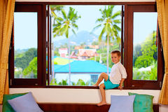 Cute boy sitting on window sill in tropics Royalty Free Stock Photography