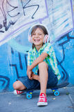 Cute boy with skateboard outdoors, standing on the street with different colorful graffiti on the walls Royalty Free Stock Images