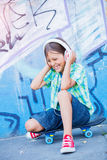Cute boy with skateboard outdoors, standing on the street with different colorful graffiti on the walls Stock Photos