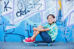 Cute boy with skateboard outdoors, standing on the street with different colorful graffiti on the walls Royalty Free Stock Photo