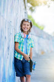 Cute boy with skateboard outdoors, standing on the street with different colorful graffiti on the walls Royalty Free Stock Photography