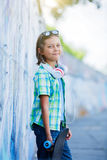 Cute boy with skateboard outdoors, standing on the street with different colorful graffiti on the walls Stock Photography