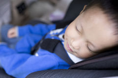 Cute boy sleeping in car within safety seat Stock Image