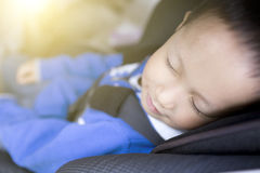 Cute boy sleeping in car within safety seat Royalty Free Stock Photography