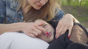 Portrait cute boy sleeping in mother`s hands, the woman caress hair of her child in the park. Leisure outdoors. Cute boy sleeping in mother`s hands, the woman stock video footage