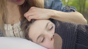 Portrait pretty boy sleeping in mother`s hands, the woman caress hair of her child in the park. Leisure outdoors. Cute boy sleeping in mother`s hands, the woman stock video footage