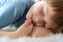 Cute boy sleeping on white fur. Royalty Free Stock Images