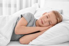 Cute boy sleeping on white pillow. At home royalty free stock photos