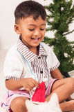 Cute boy smile and play christmas tree background Stock Photos