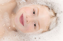 Cute boy smiling in bath tub Stock Photo