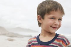 Cute Boy Smiling At Beach. Closeup of cute little boy smiling while looking away at beach Royalty Free Stock Photos