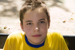 Cute boy smiling at camera in the park. On a sunny day Stock Image