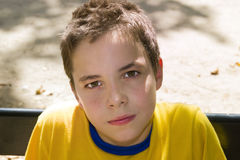 Cute boy smiling at camera in the park. On a sunny day Royalty Free Stock Photo