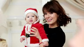 Cute boy smiling for mother, Little kid on the hands of the mother, the child dressed in a carnival costume of Santa stock video