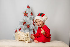 Cute boy smiling next to Christmas tree Royalty Free Stock Image