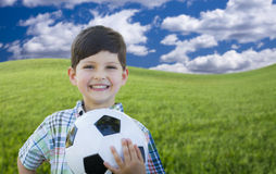 Cute Boy with Soccer Ball in a Grassy Field Stock Photos