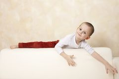 Cute boy on a sofa. Portrait of cute happy boy lying on a sofa Royalty Free Stock Images
