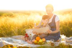 Cute boy son and his beautiful pregnant mother on a picnic on a beautiful autumn or summer day read a book Stock Image